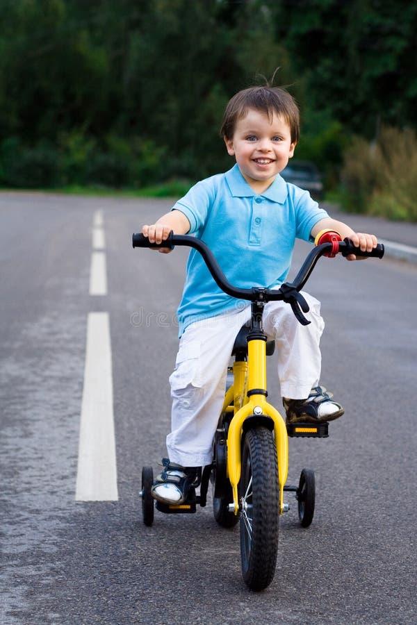 Un pequeño ciclista en el viaje en el camino foto de archivo