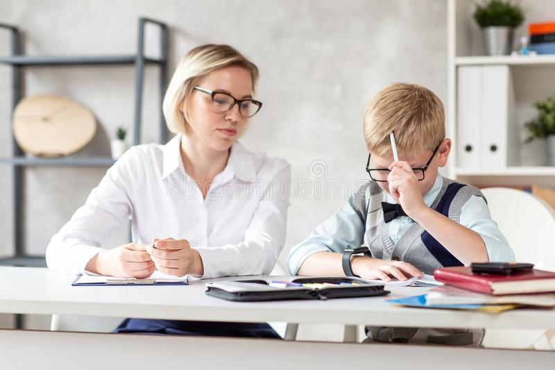 Un pequeño colegial está pensando en el ejercicio mientras que su profesor se está sentando al lado de él fotos de archivo libres de regalías