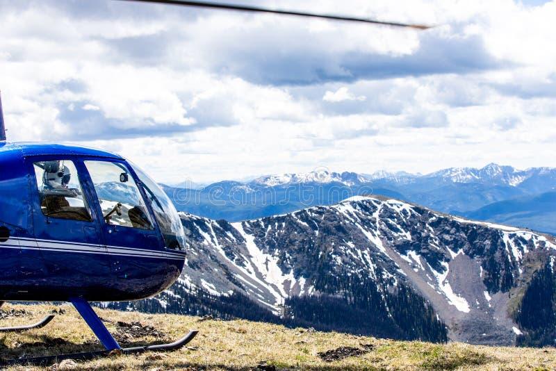 Un pequeño helicóptero azul en las montañas de la Columbia Británica fotos de archivo libres de regalías