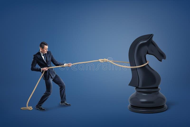 Un pequeño hombre de negocios coge a un caballero negro grande del ajedrez con un lazo de la cuerda fotos de archivo libres de regalías