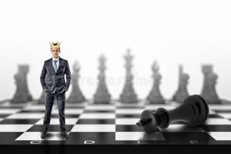 Un pequeño hombre de negocios con una corona de oro en su cabeza se coloca en un tablero de ajedrez cerca de un rey negro caido imagen de archivo