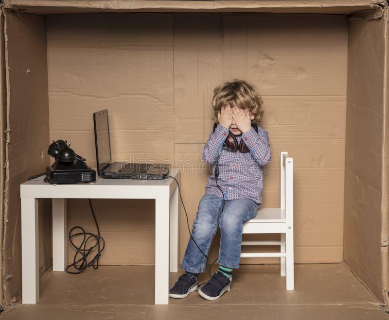 Un pequeño hombre de negocios cubre sus ojos del cansancio imagen de archivo