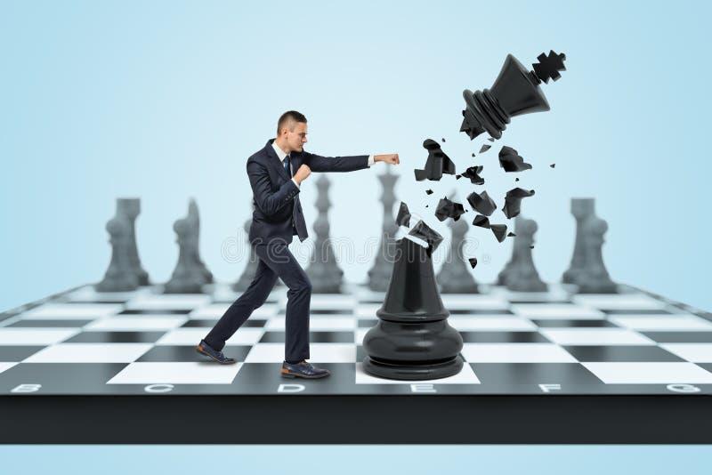 Un pequeño hombre de negocios se coloca en un tablero de ajedrez y golpea a un rey negro grande y lo destruye en pequeños pedazos foto de archivo libre de regalías