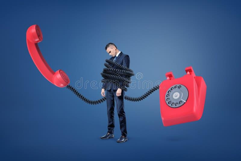 Un pequeño hombre de negocios se coloca encuadernado por un cordón plástico enorme de un teléfono retro rojo gigante fotografía de archivo