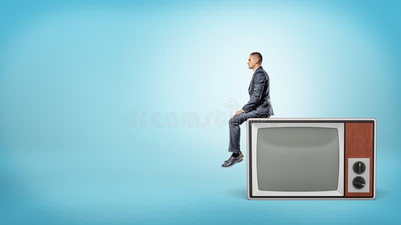 Un pequeño hombre de negocios se sienta en vista lateral en un aparato de TV retro gigante con la pantalla en blanco imagenes de archivo