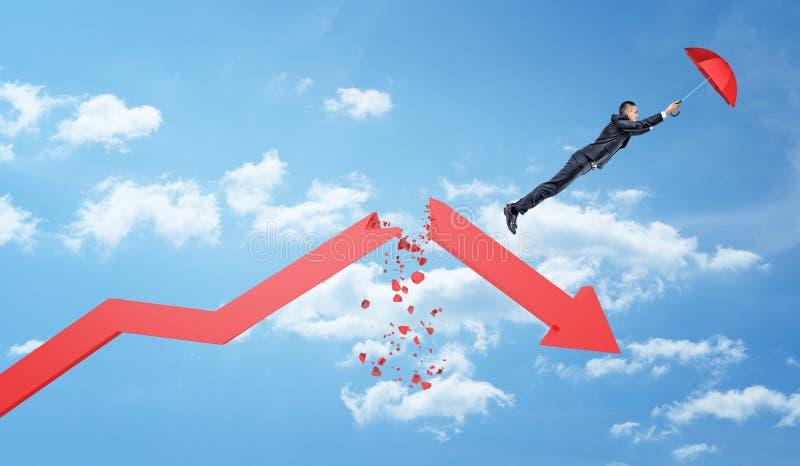 Un pequeño hombre de negocios sostiene un paraguas rojo y vuela lejos de una flecha roja grande de la estadística rota por la mit fotografía de archivo libre de regalías