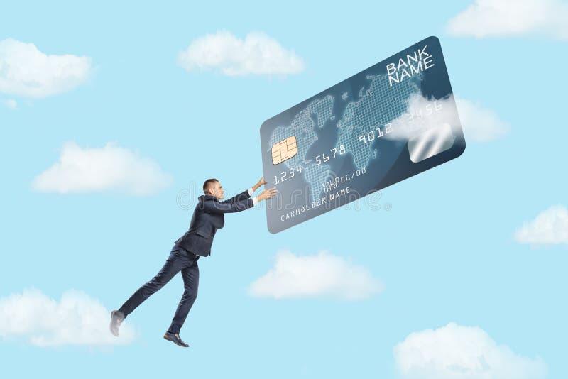 Un pequeño hombre de negocios vuela en el cielo y ase una tarjeta de crédito gigante en un salto Vida para el dinero imágenes de archivo libres de regalías
