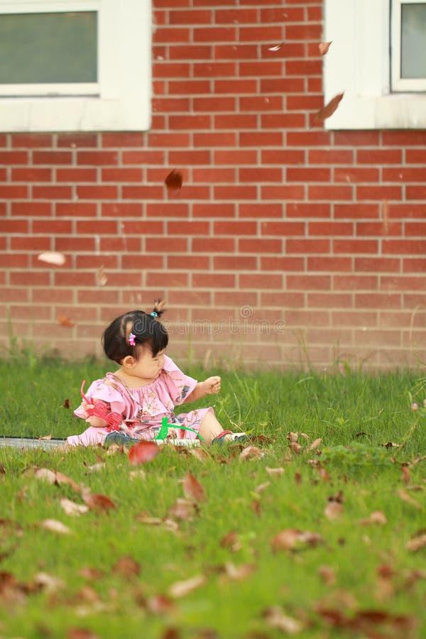 Un pequeño juego chino del bebé se va en el césped imagenes de archivo