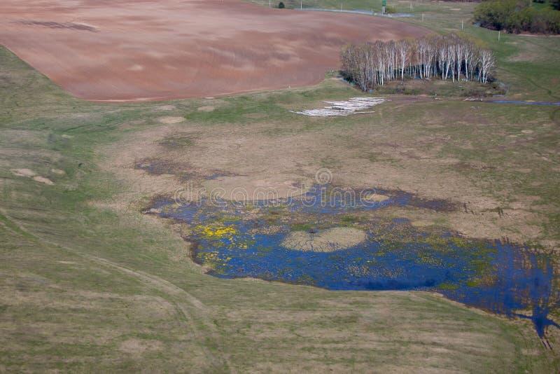 Un pequeño lago al borde de un campo arado imagen de archivo