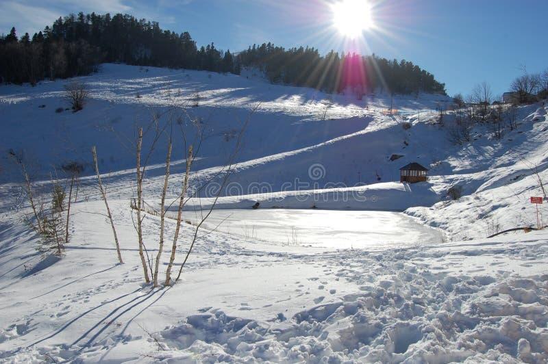 Un pequeño lago helado de la montaña después de un invierno congelado foto de archivo