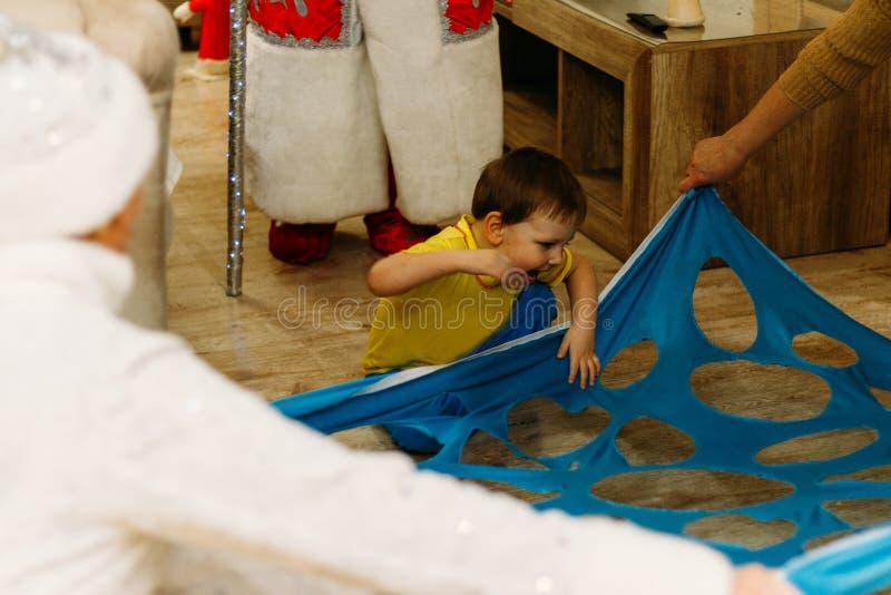 un pequeño muchacho camina encima, las subidas, carriles, pasos en un agujero, un corte, una abertura en una tela azul, en materi fotografía de archivo