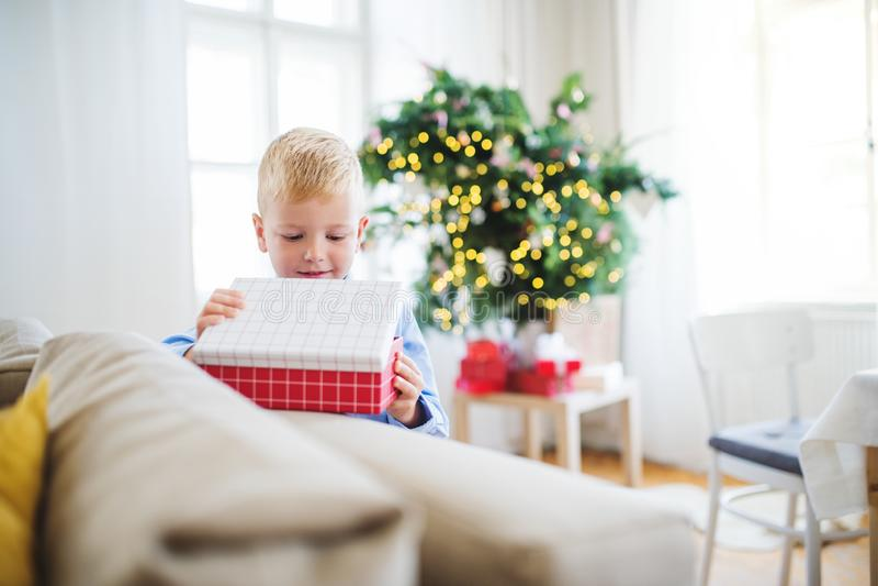 Un pequeño muchacho con la apertura de un presente en casa en el tiempo de la Navidad imagen de archivo libre de regalías