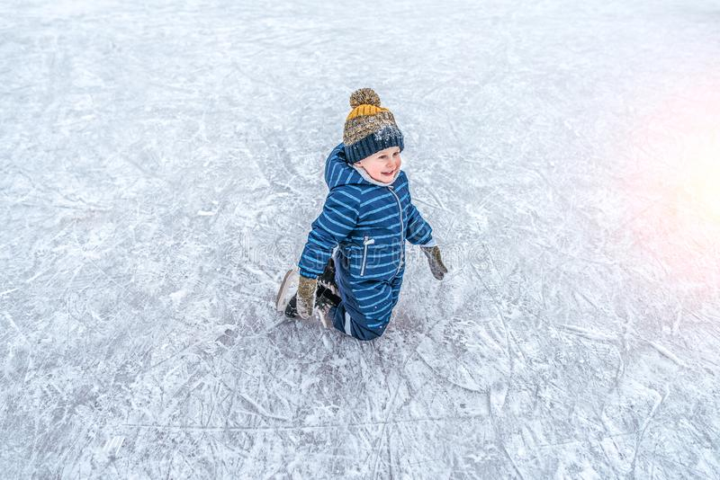 Un pequeño muchacho de 4-6 años, arrodillándose, patinando, en el invierno en la ciudad en una pista de hielo Sonrisa feliz, inte fotos de archivo libres de regalías