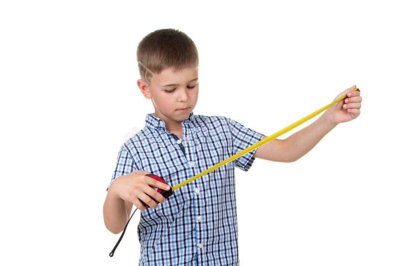 Un pequeño muchacho hermoso del constructor en camisa a cuadros azul mira a una cinta métrica, aislada en el fondo blanco foto de archivo libre de regalías