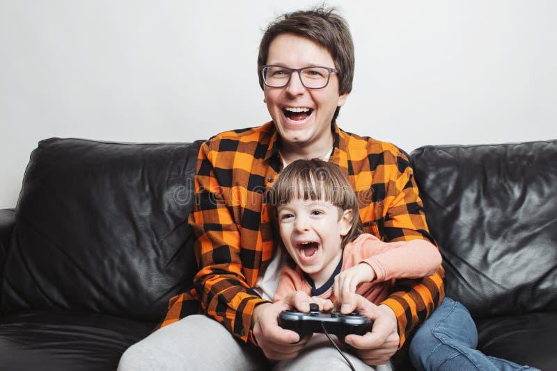 Un pequeño muchacho hermoso y su papá se están sentando en el sofá en casa y están jugando a los videojuegos con la palanca de ma fotos de archivo