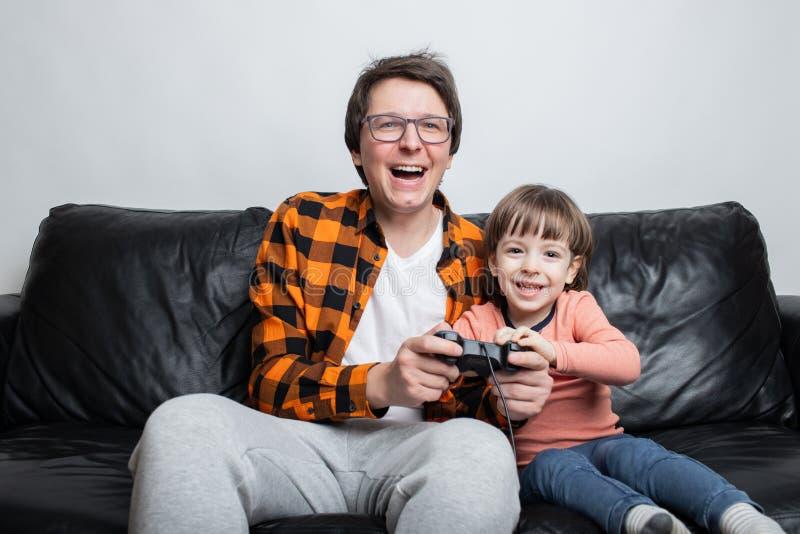 Un pequeño muchacho hermoso y su papá se están sentando en el sofá en casa y están jugando a los videojuegos con la palanca de ma foto de archivo