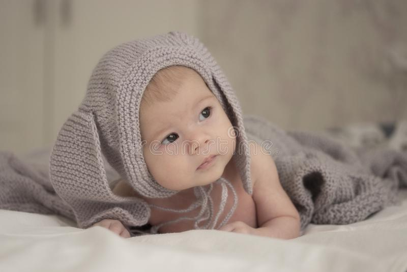 Un pequeño niño de 1 mes en un sombrero gris con los oídos mira al lado Foco suave ligero suave imágenes de archivo libres de regalías