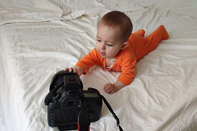 Un pequeño niño del bebé juega con una cámara grande y la mentira en la cama fotos de archivo