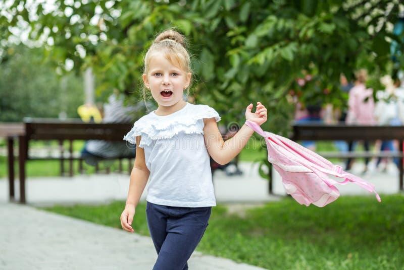 Un pequeño niño está caminando abajo de la calle con una mochila El concepto de escuela, estudio, educación, niñez foto de archivo