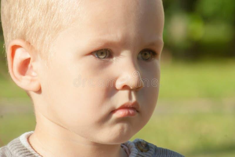Un pequeño niño pequeño está trastornado, triste, enfocado y serio Ofenden al niño fotografía de archivo libre de regalías