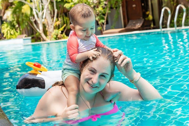 Un peque?o ni?o feliz en un ba?ador se sienta en los hombros de la madre y los juegos con el pelo en su cabeza, tiran del pelo imagen de archivo libre de regalías