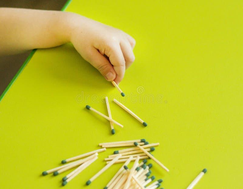 Un pequeño niño lleva a cabo un partido en la mano en un fondo, un primer, un peligro, un fuego, un niño y partidos verdes imagen de archivo libre de regalías