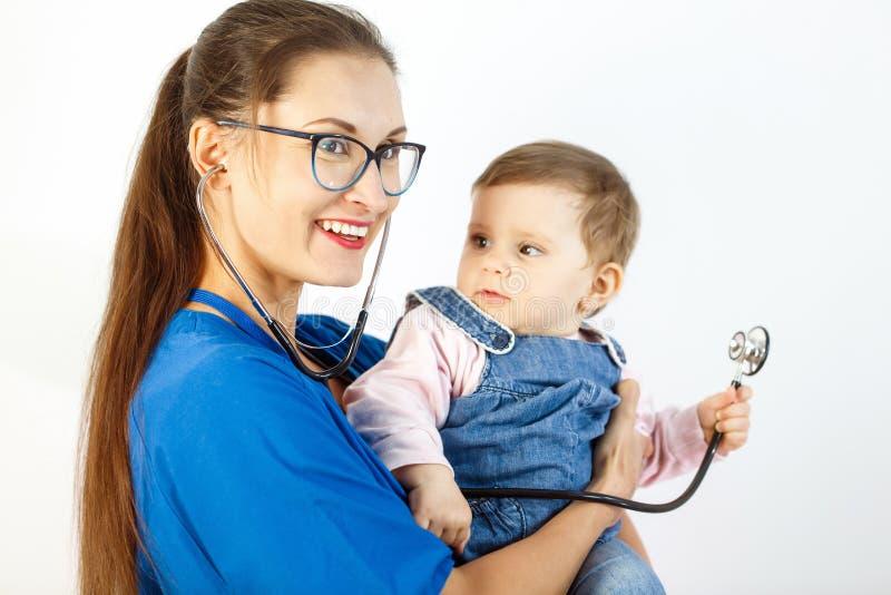 Un pequeño niño mira el doctor y los juegos con un estetoscopio en sus brazos imagen de archivo