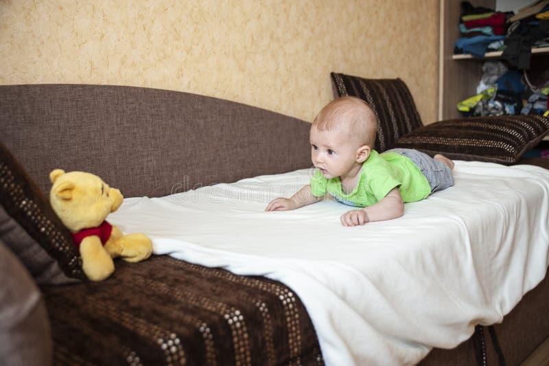 Un pequeño niño mira el juguete con sorpresa foto de archivo