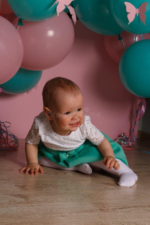 Un pequeño niño, muchacha, bebé, se sienta en el piso en un vestido blanco y azul, contra un fondo del aire azul y rosado, las bo fotos de archivo libres de regalías