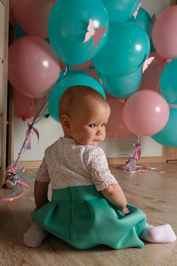 Un pequeño niño, muchacha, bebé, se sienta en el piso en un vestido blanco y azul, contra un fondo del aire azul y rosado, las bo fotografía de archivo