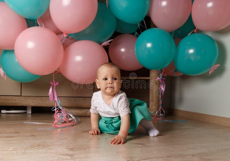 Un pequeño niño, muchacha, bebé, se sienta en el piso en un vestido blanco y azul, contra un fondo del aire azul y rosado, las bo fotografía de archivo libre de regalías