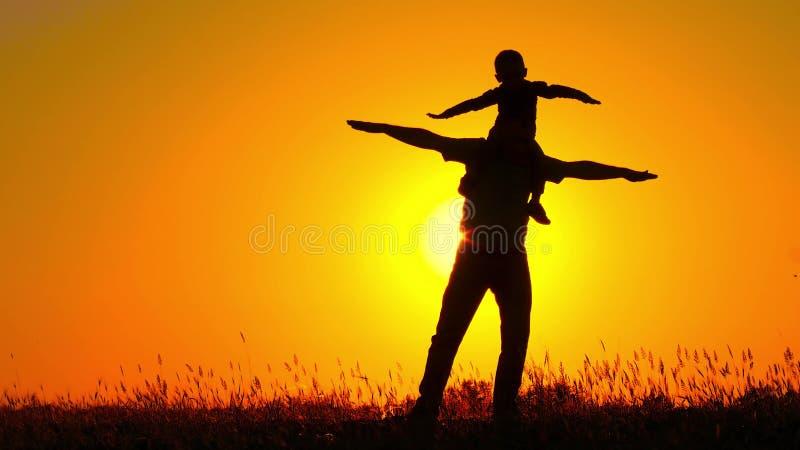 Un pequeño niño que hace girar en su ` s del padre lleva a hombros Familia feliz que juega en la puesta del sol Silueta imagen de archivo libre de regalías