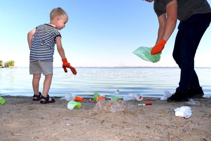 Un pequeño niño recoge basura en la playa Su papá señala su finger donde lanzar la basura Los padres enseñan los niños a limpieza fotografía de archivo libre de regalías