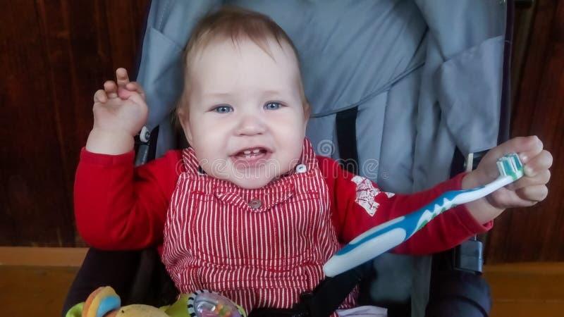 Un pequeño niño pequeño se sienta en un cochecito y juega con un cepillo de dientes imagen de archivo