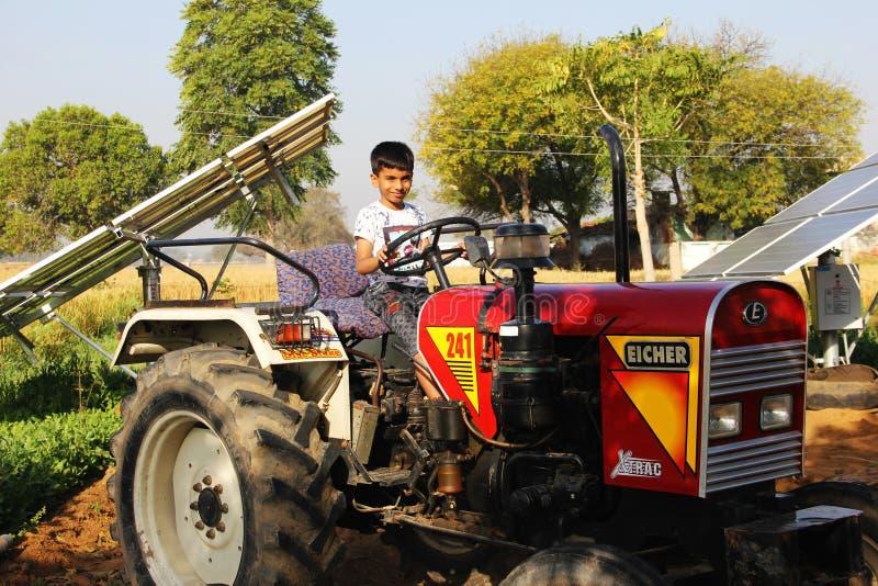 Un pequeño niño sentarse en el tractor en pueblo rural en la India fotos de archivo libres de regalías