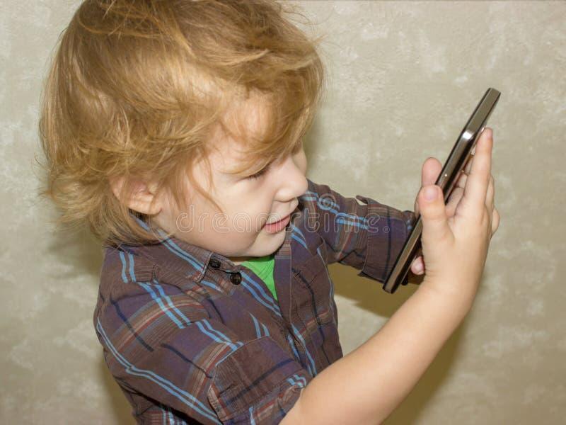 Un pequeño niño pequeño sostiene un artilugio en sus manos y hace clic en la pantalla del smartphone fotos de archivo