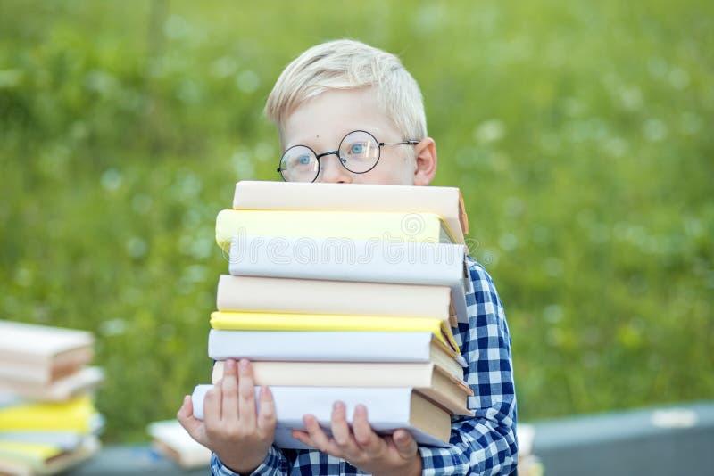 Un pequeño niño sostiene muchos libros en sus manos El concepto de aprendizaje, de escuela, de mente, de forma de vida y de éxito fotos de archivo libres de regalías