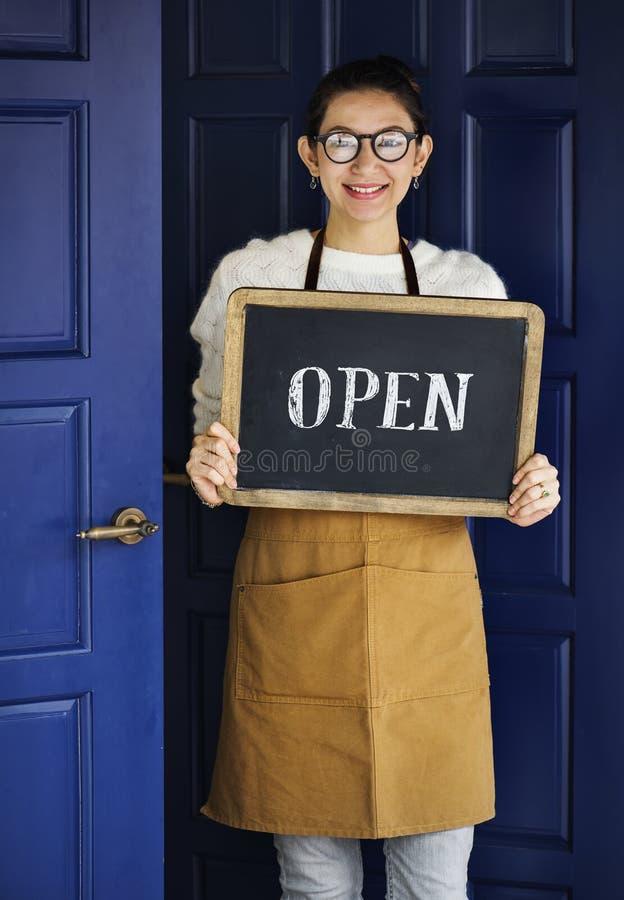Un pequeño propietario de negocio alegre con la muestra abierta imagen de archivo libre de regalías