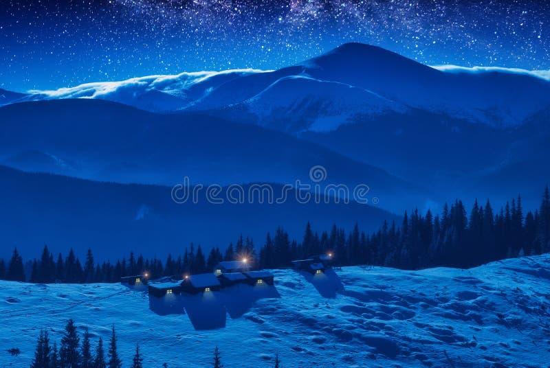 Un pequeño pueblo en un canto nevado de la montaña imagen de archivo