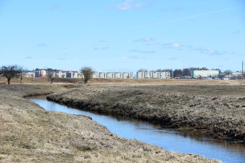 Un pequeño río fluye cerca de la ciudad en la primavera foto de archivo libre de regalías