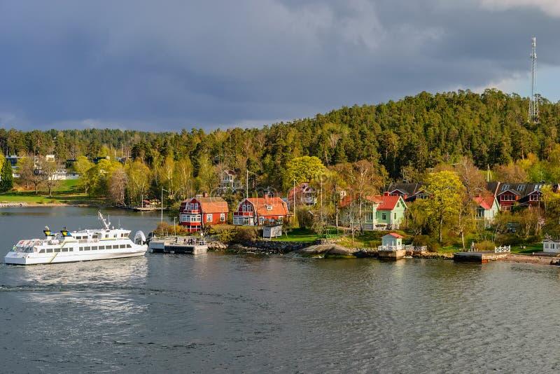 Un pequeño transbordador de pasajero suburbano Varmdo, transporte público de la ciudad de Estocolmo, llega al embarcadero del tra fotos de archivo libres de regalías