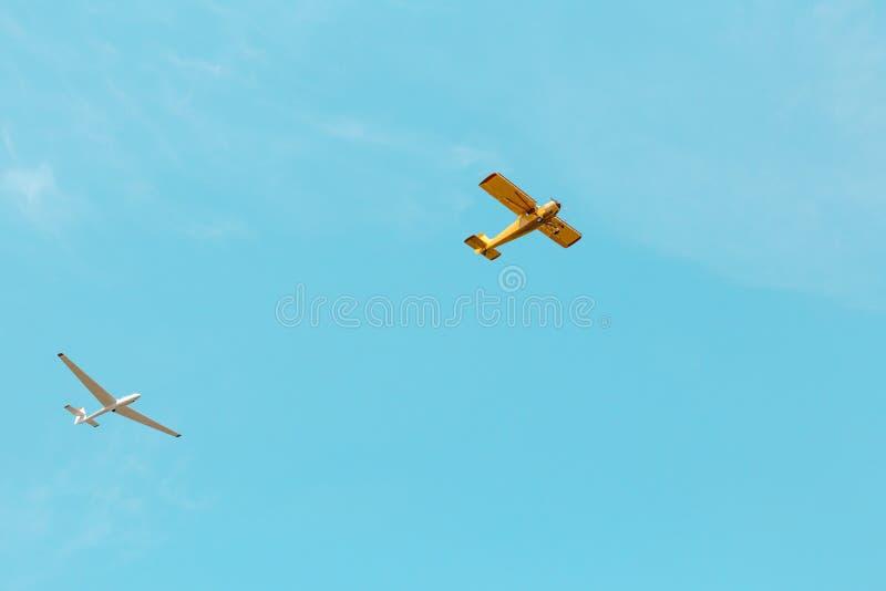 Un pequeño vuelo amarillo del avión y del planeador a través del cielo azul foto de archivo libre de regalías