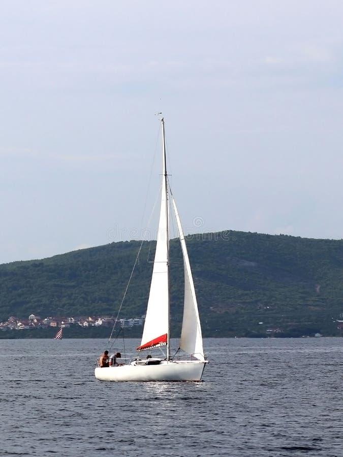 Un pequeño yate de los deportes de la navegación de la navegación diurna está navegando con tres dueños de un yate a lo largo de  fotos de archivo libres de regalías