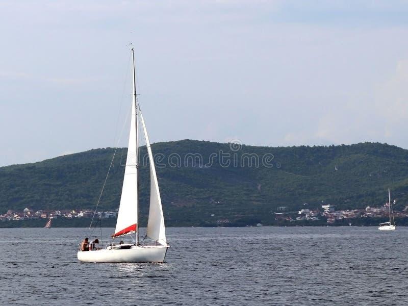 Un pequeño yate de los deportes de la navegación de la navegación diurna está navegando con tres dueños de un yate a lo largo de  fotografía de archivo