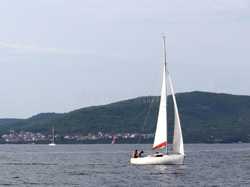 Un pequeño yate de los deportes de la navegación de la navegación diurna está navegando con tres dueños de un yate a lo largo de  imagen de archivo libre de regalías