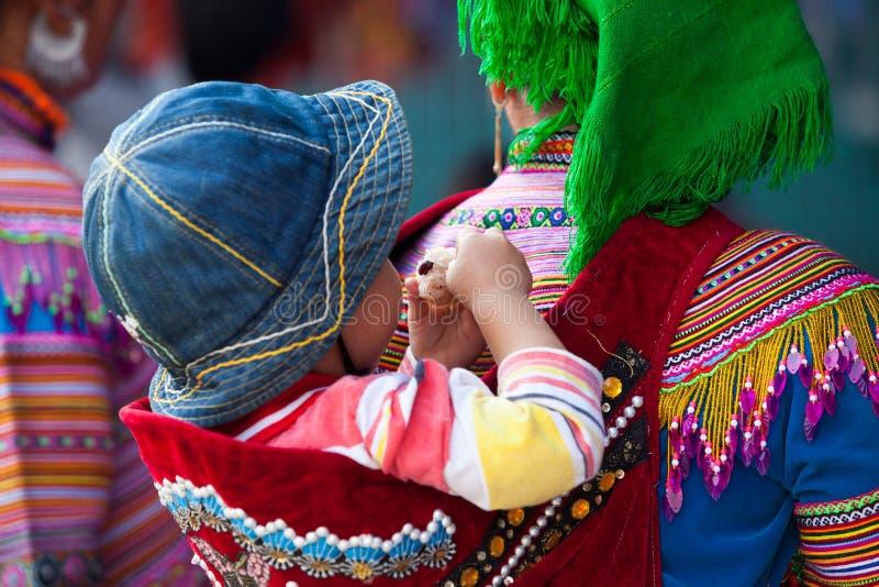 Un pequeños Hmong y x28; Miao& x29; niño en su bajar trasero de la madre a la ciudad foto de archivo libre de regalías
