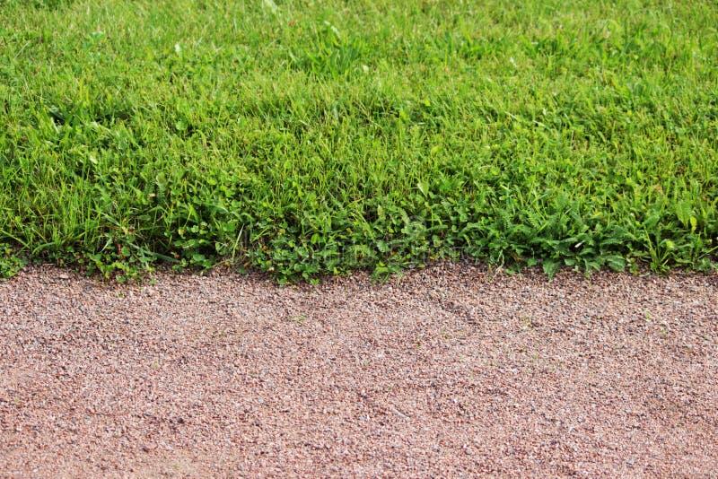 Un percorso di ghiaia e un prato inglese di erba verde tagliata nel parco di Gatcina immagini stock