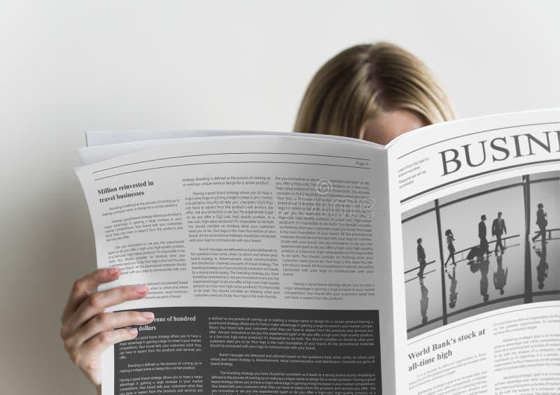 Un periódico de negocios de la lectura de la mujer foto de archivo libre de regalías