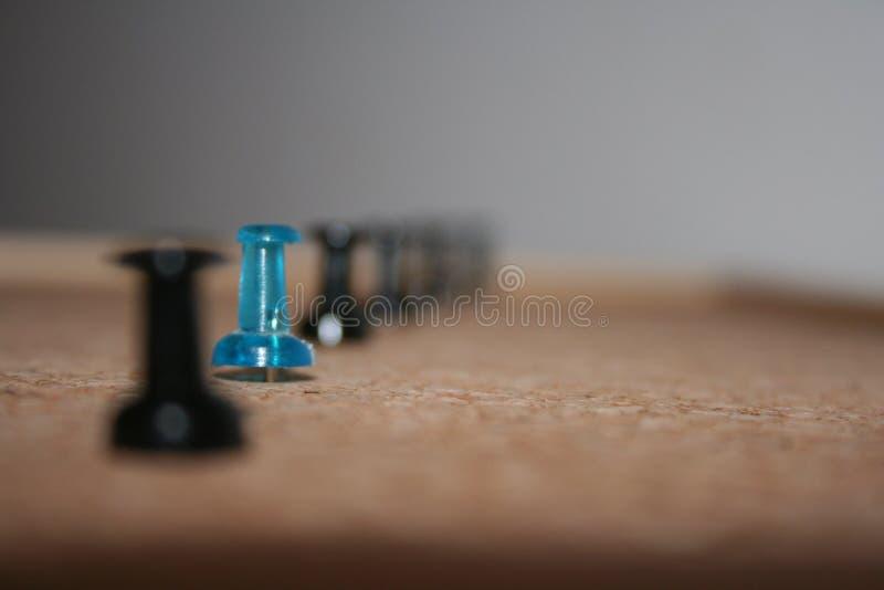 Un perno azul entre negro unos en el corcho-tablero fotos de archivo