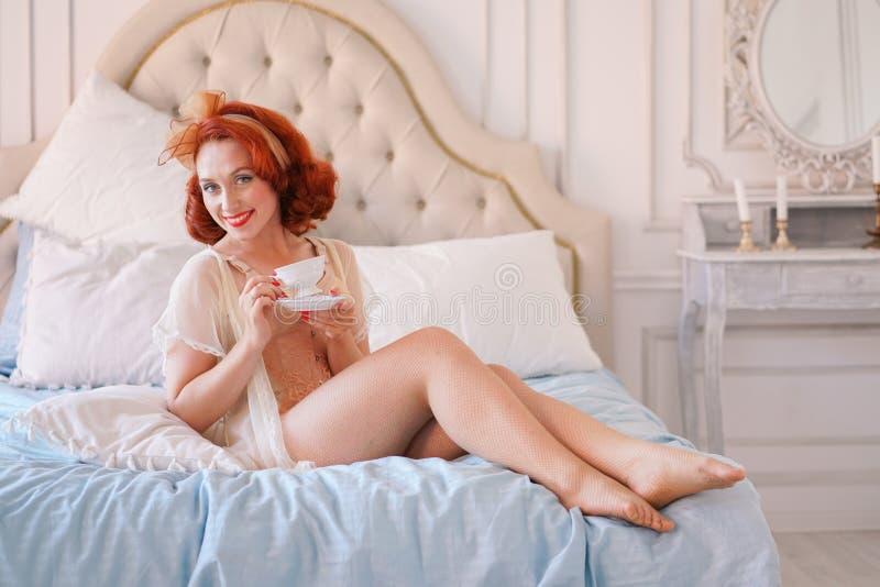 Un perno lussuoso su signora vestita in una biancheria d'annata beige che posa nella sua camera da letto ed ha una tazza del tè d immagine stock